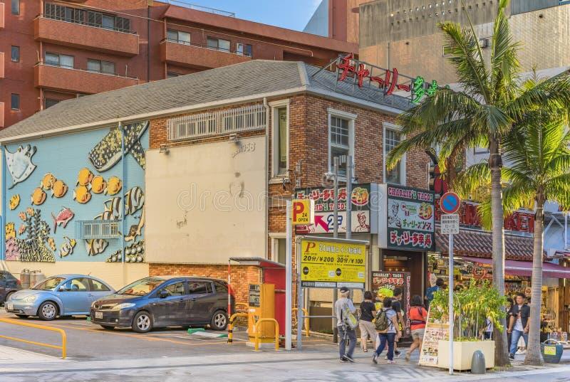 De straat van Kokusaidori wat internationale die straat betekent met twee beeldhouwwerken van de shisaleeuw in de stad van Naha i royalty-vrije stock foto