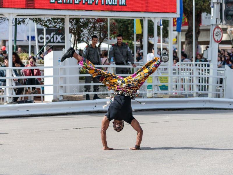 De straatdanser toont zijn kunst bij het festival van Adloyada gekleed als verkenners met trommels in Nahariyya, Israël gaat stock afbeeldingen