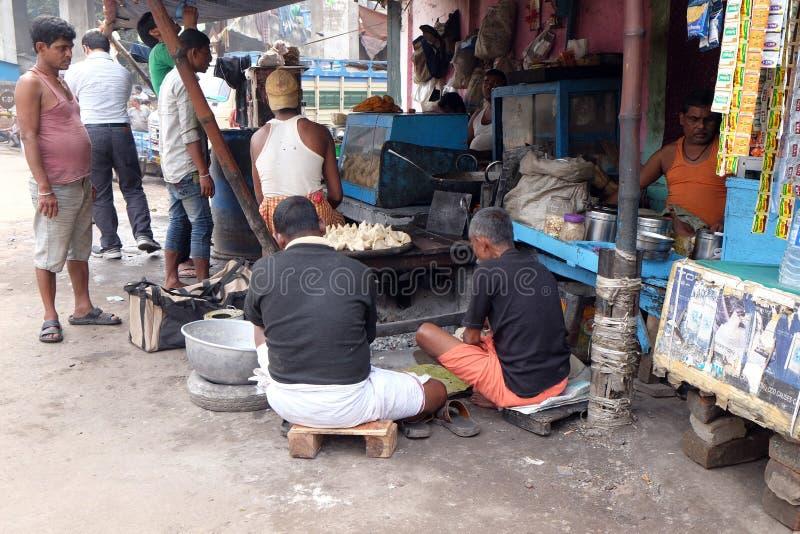 De straathandelaar verkoopt snel voedsel voor hongerige mensen op de bezige straat in Kolkata stock fotografie