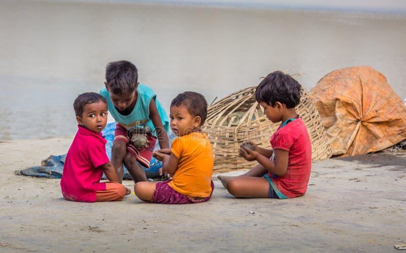 De straatjonge geitjes spelen met klei in Mallick Ghat, bloemmarkt, Kolkata, India Dit ghat wordt gevestigd dichtst aan de brug v stock afbeeldingen