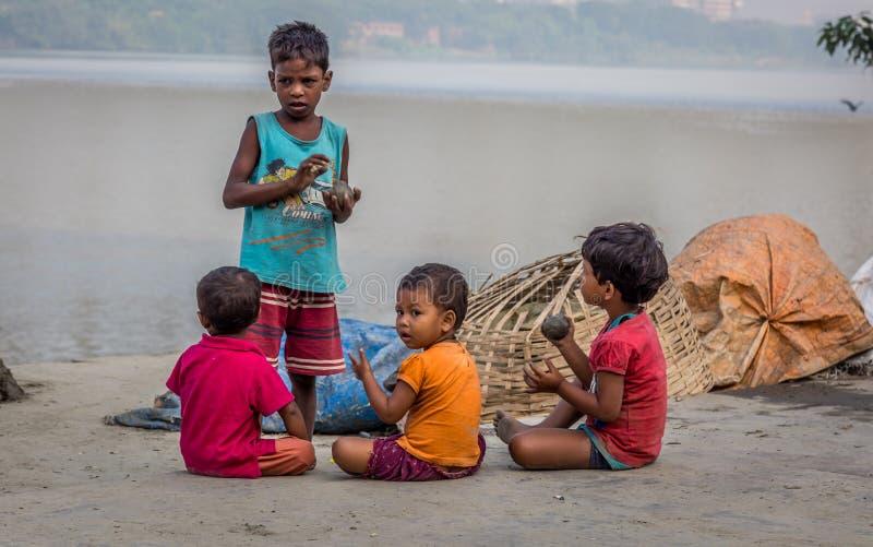 De straatkinderen spelen met klei van de de rivierbank van Ganges in Mallick Ghat, bloemmarkt, Kolkata, India stock fotografie