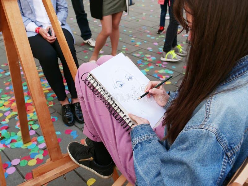 De straatkunstenaar trekt potloodportret levend van mensen royalty-vrije stock afbeelding