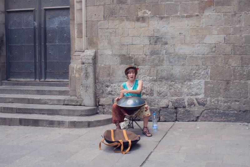 De straatmusicus speelt een muzikaal instrument hangt stock foto