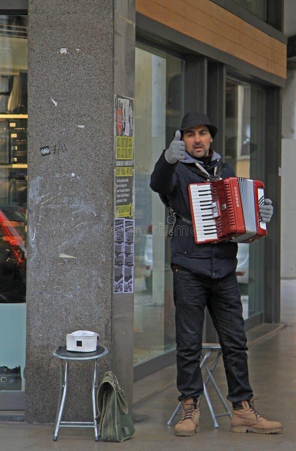De straatmusicus toont een duim aan iemand stock foto
