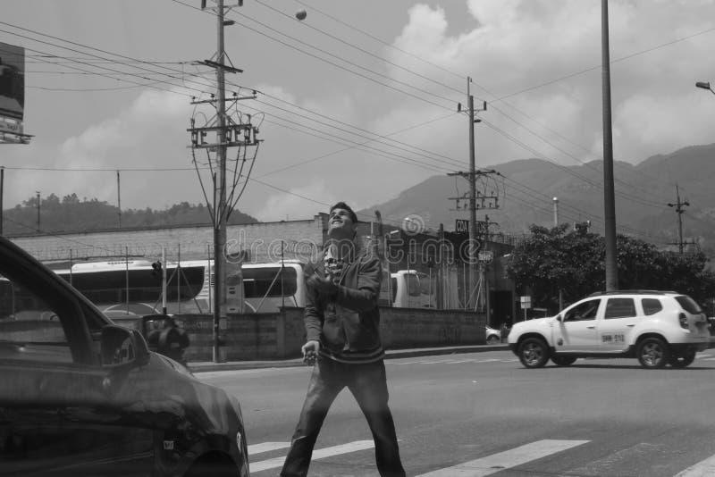 De straatuitvoerder jongleert met bij een rood licht stock foto's