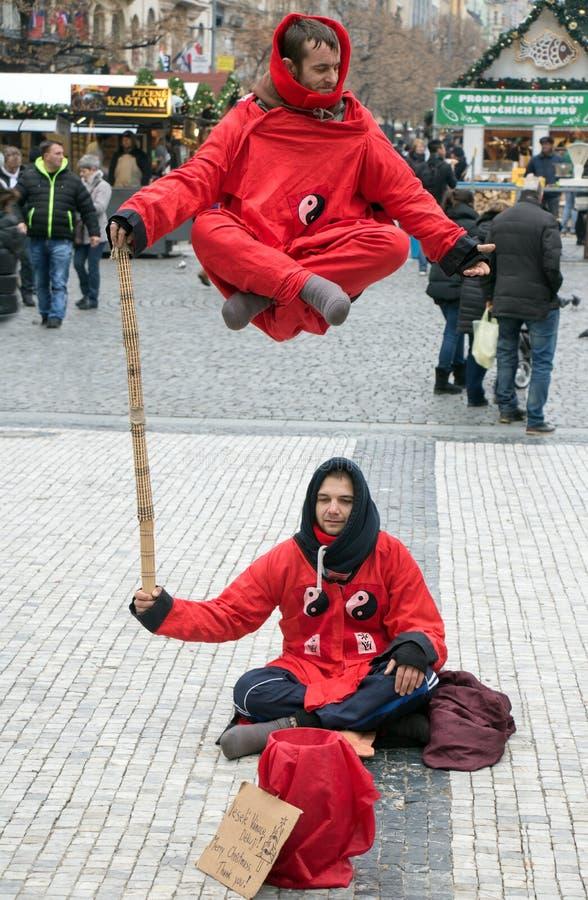 De straatuitvoerders kleedden zich aangezien de monniken maken levitatie tonen stock foto's