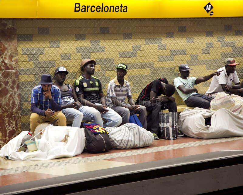 De straatventers met grote balen wachten op een trein in de metro stock foto's