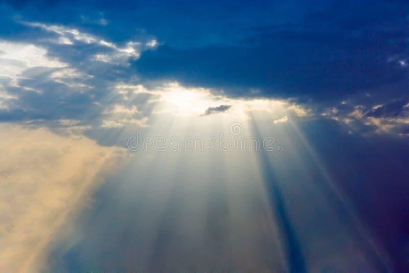 De stralen van de zon zijn slaand door de wolken stock fotografie