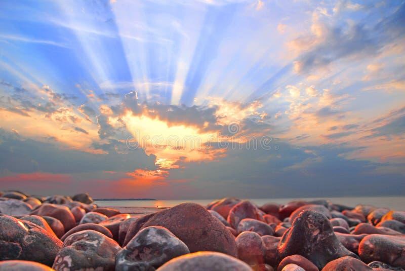 De stralen van de wolkbreukzon bij zonsondergang op whitstable strand stock foto's