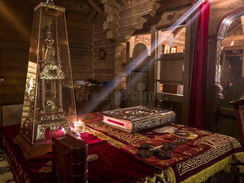 De stralen van de zon maken hun manier door de vensters en de barsten van de Orthodoxe kerk op de troon en heilig royalty-vrije stock foto's