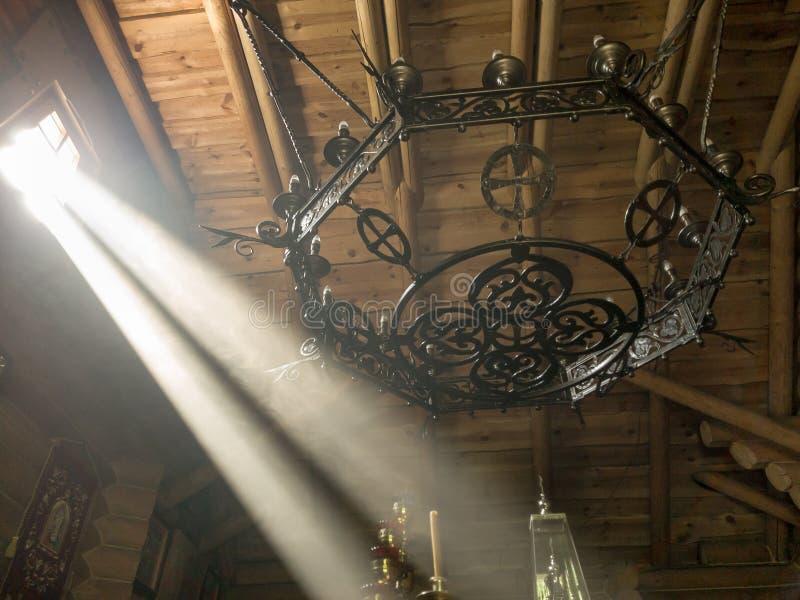 De stralen van de zon maken hun manier door de vensters en de barsten van de Orthodoxe kerk op de troon en heilig stock afbeelding