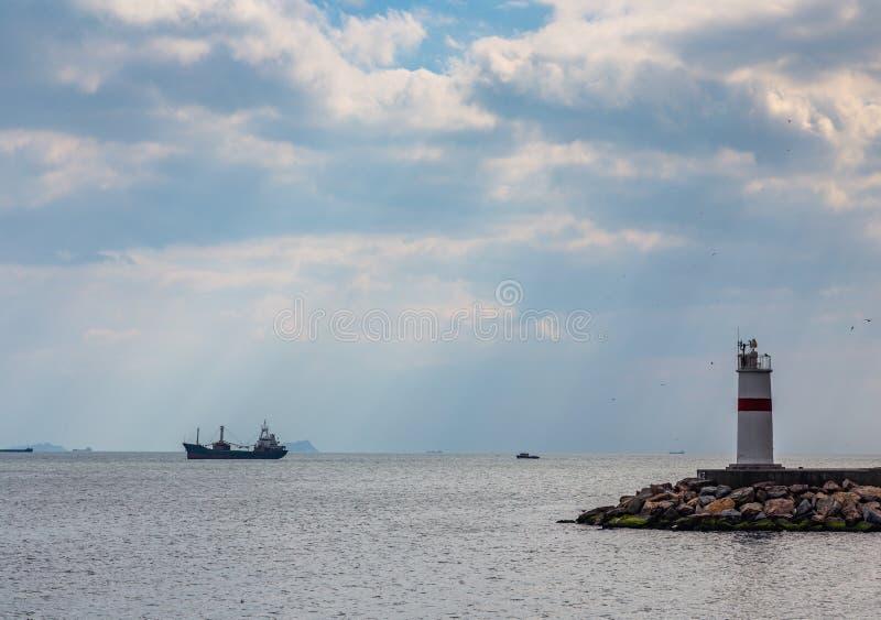 De stralen van de zon verlichten de vuurtoren en het schip in de wegen door de wolken bij de ingang aan Bosphorus, stock fotografie