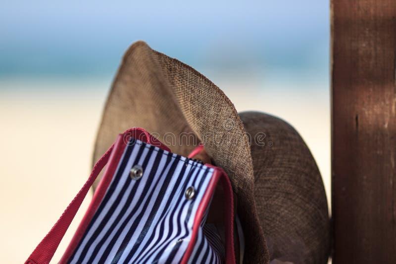 De strandzak en de hoed zijn in de schaduw royalty-vrije stock afbeeldingen