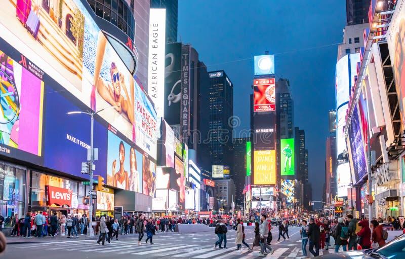 De straten van New York, Manhattan bij nacht Verlichte hoge gebouwen, het kleurrijke neonlichten, advertenties en mensen lopen royalty-vrije stock afbeeldingen