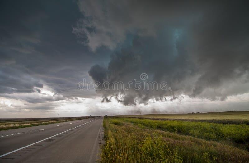 De strenge winden van een donkere onweerswolk blazen vuil over een weg op de vlaktes stock foto's