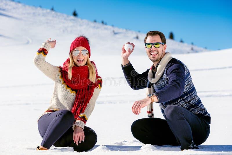 De strijd van de sneeuwbal Het paar dat van de winter pret het spelen in sneeuw heeft in openlucht Jong blij gelukkig multi-racia royalty-vrije stock foto's