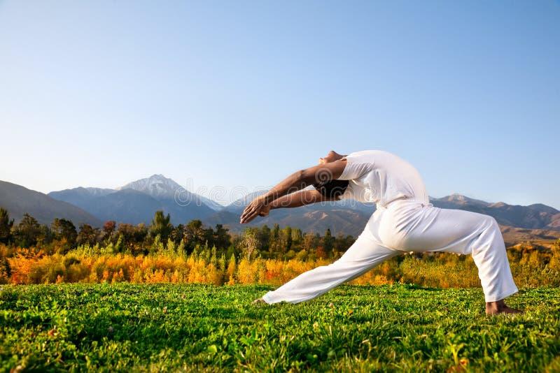 De strijder van de yoga stelt in bergen stock afbeeldingen
