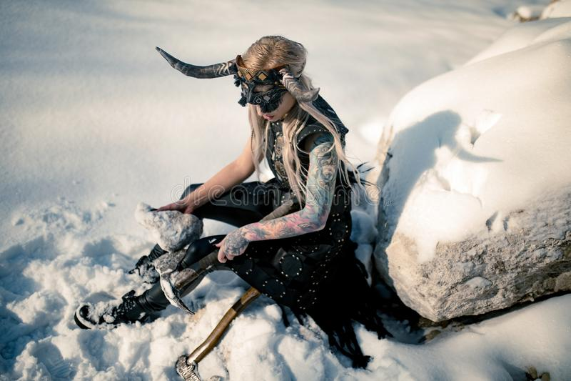 De strijdersvrouw in beeld van Viking met gehoornde helm en bijl zit op sneeuw naast grote steen royalty-vrije stock foto
