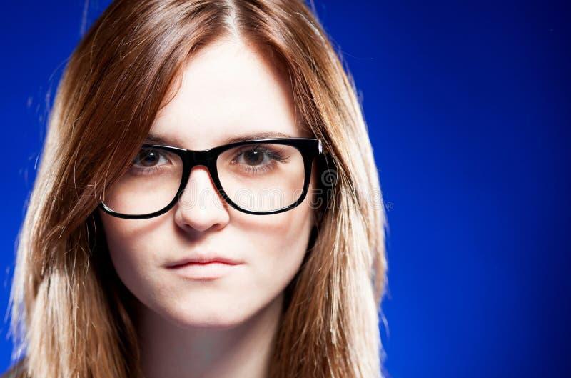 De strikte jonge vrouw van de close-up met nerdglazen stock foto