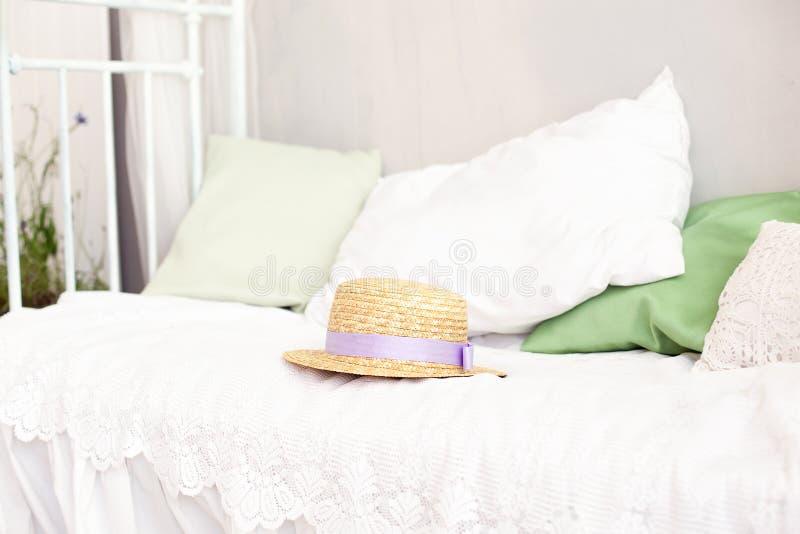 De strohoed ligt op het witte beddegoed op het bed Het concept van het de zomerweekend Vrije tijd, weekend, reis Vrouwentoebehore stock fotografie