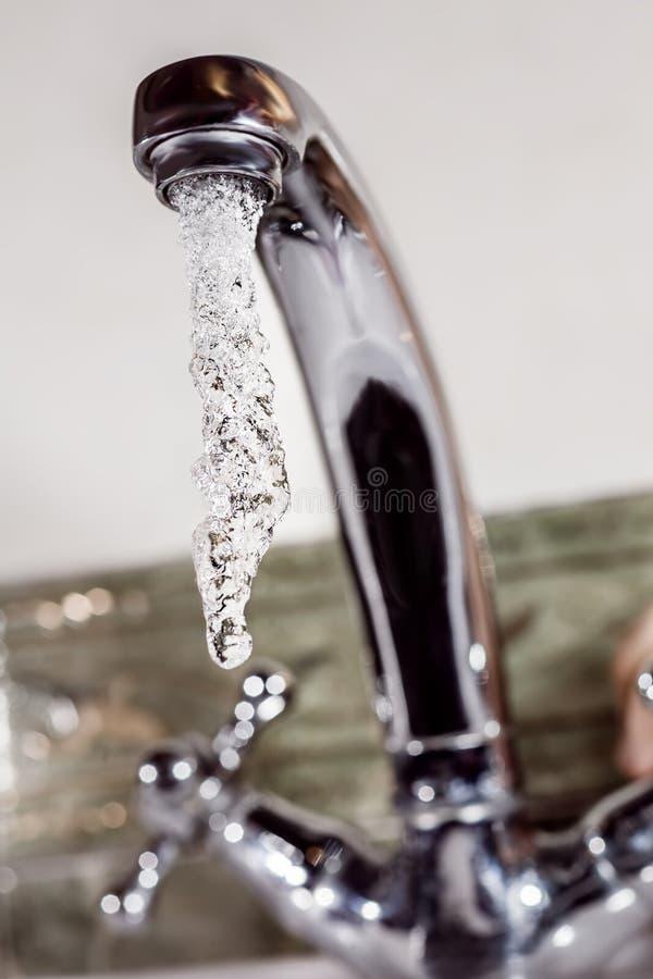 De stromen van het water van de kraan stock foto