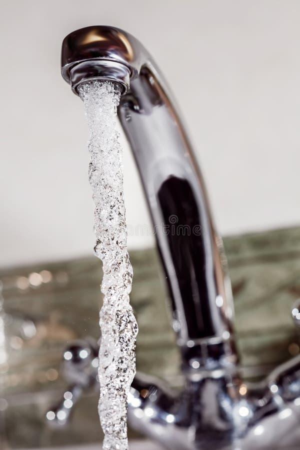 De stromen van het water van de kraan royalty-vrije stock afbeeldingen