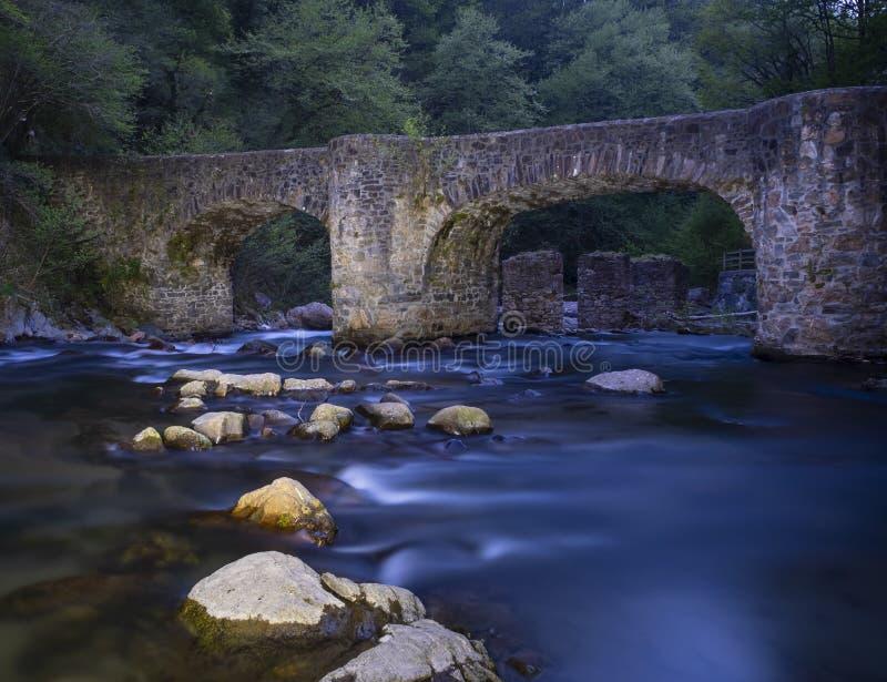 De stromen van de Leizaranrivier tussen de rotsen onder een oude brug in Andoain royalty-vrije stock afbeeldingen