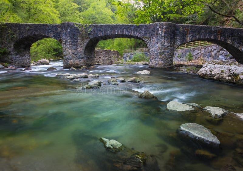 De stromen van de Leizaranrivier tussen de rotsen onder een oude brug in Andoain stock foto