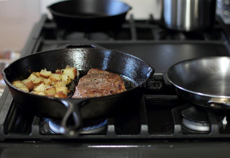 De strooklapje vlees van New York het braden in een gietijzerpan met aardappels royalty-vrije stock foto