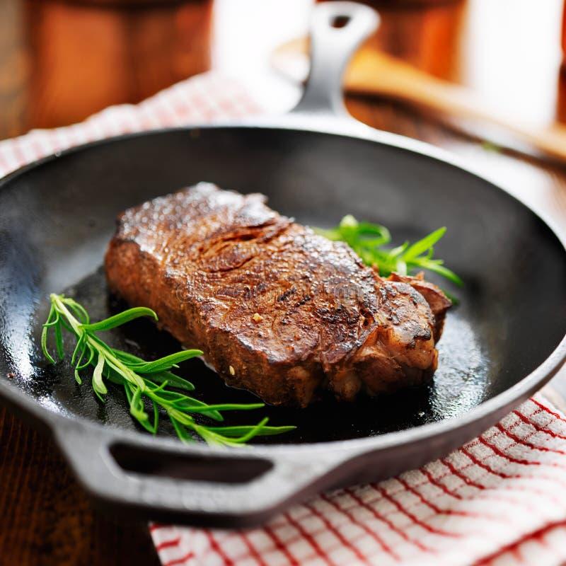 De strooklapje vlees van New York in ijzerkoekepan die wordt gekookt stock foto's