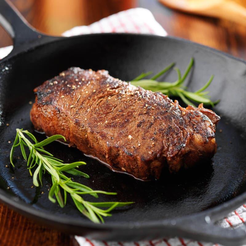De strooklapje vlees van New York in ijzerkoekepan die wordt gekookt stock foto