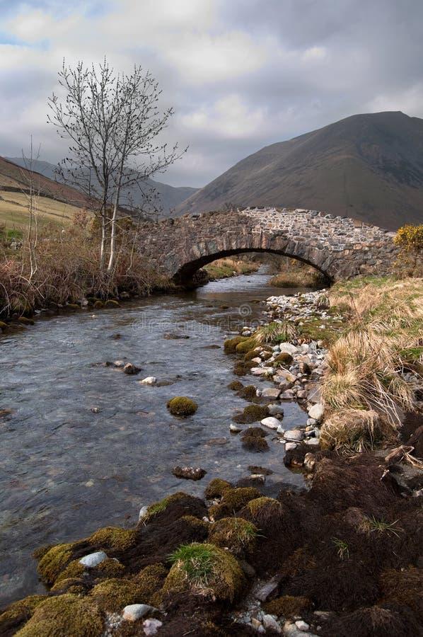 De Stroom die van de berg onder een steenbrug stroomt stock fotografie