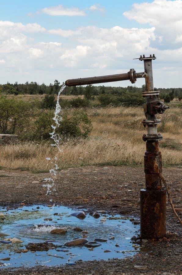 De stroom die van water van de aan het licht gebrachte tapkraan wegvloeien royalty-vrije stock foto