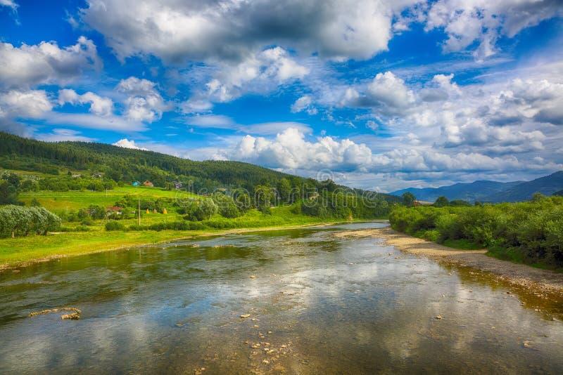 De stroom van de bergrivier van water in de rotsen met majestueus blauw s royalty-vrije stock foto's