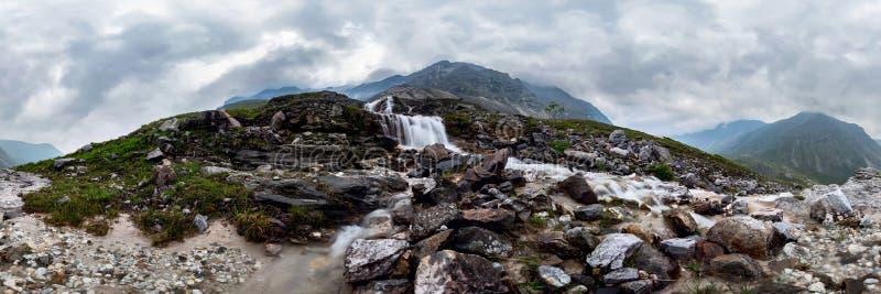 De stroom van de bergwaterval in nevelig regenachtig weer in de valleibloemen Cilindrisch panorama 360 stock foto