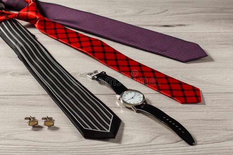 De stropdassen van de kleurenzijde, horloge, manchetknopen op een grijze houten backgrou stock fotografie