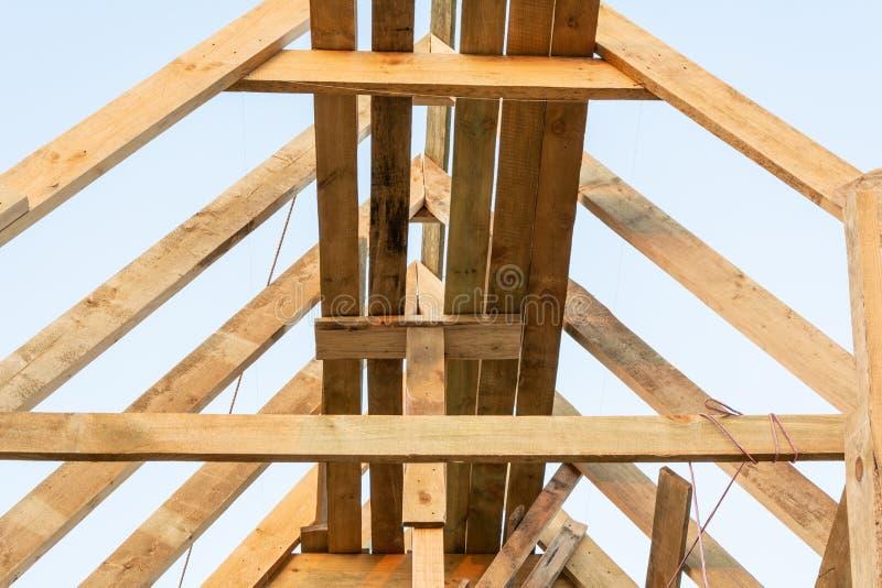 De structuur van het dakkader in houten kaderhuis in aanbouw bij zonsondergang stock afbeeldingen