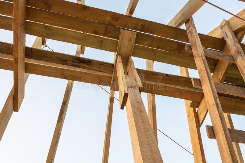 De structuur van het dakkader in houten kaderhuis in aanbouw bij zonsondergang stock afbeelding
