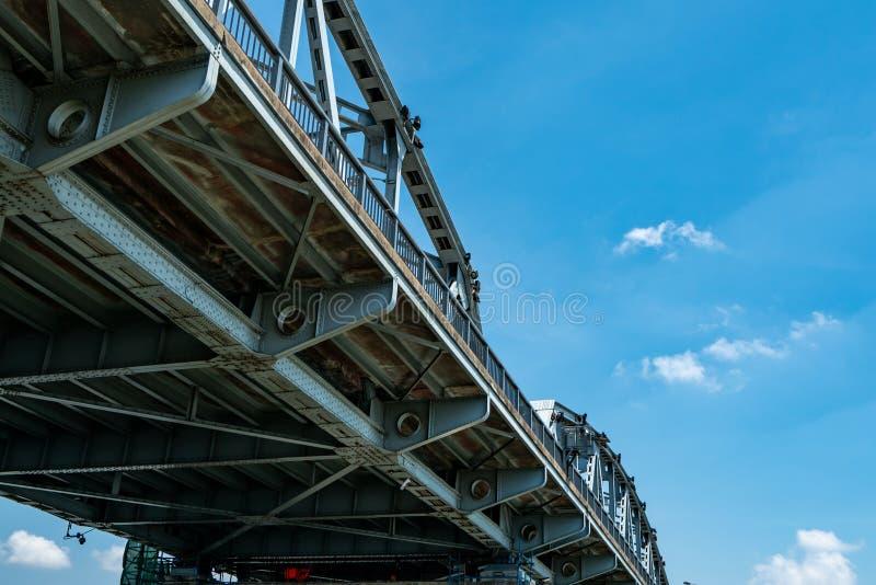 De structuur van de staalbrug tegen blauwe hemel en witte wolken De techniekbouw van de ijzerbrug De brug van het sterke en sterk royalty-vrije stock foto