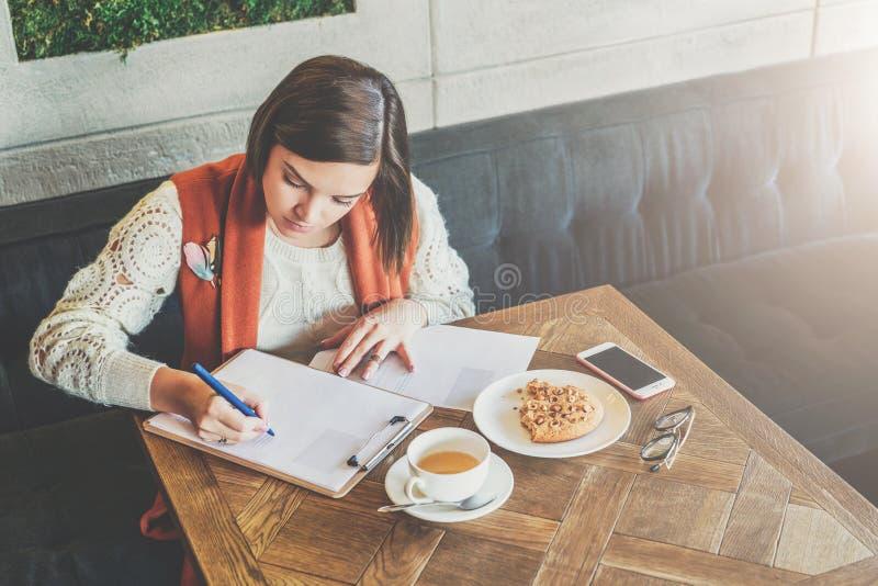 De student bestudeert online, doend thuiswerk Het meisje schrijft brief, verklaring Voor lijstkop thee, koekjes, smartphone royalty-vrije stock fotografie