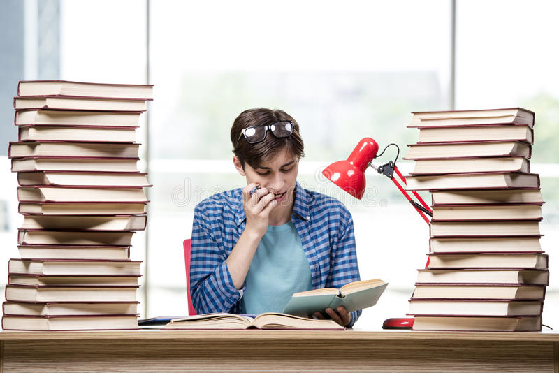 De student die met veel boeken voor examens voorbereidingen treft stock foto
