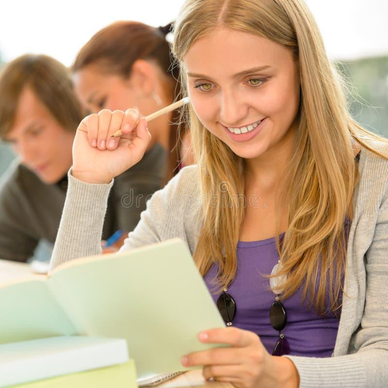 De student die van de middelbare school nota's in bibliotheekstudie neemt royalty-vrije stock foto