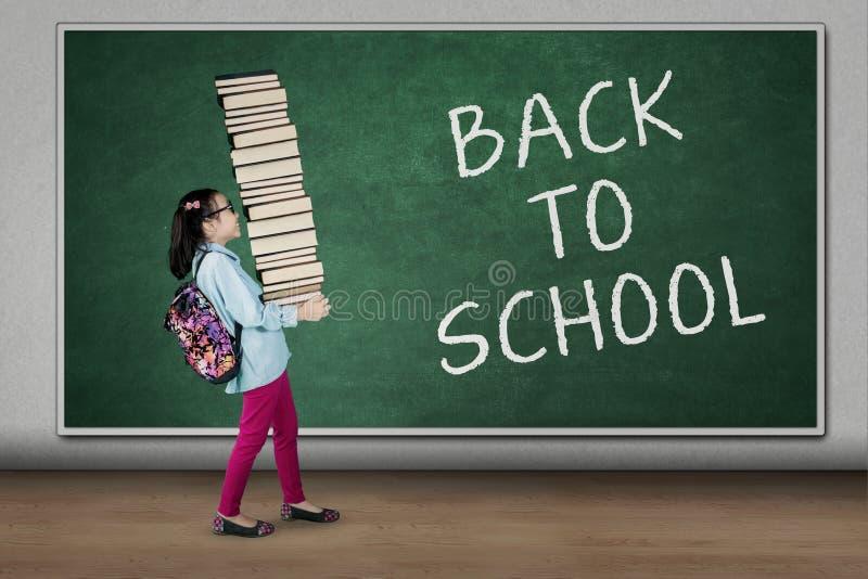 De student draagt boeken met terug naar schooltekst stock afbeelding