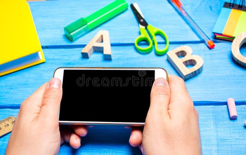 De student houdt een mobiele telefoon op de achtergrond van creatief op de Desktop knoeit de werkplaats van de student stock fotografie