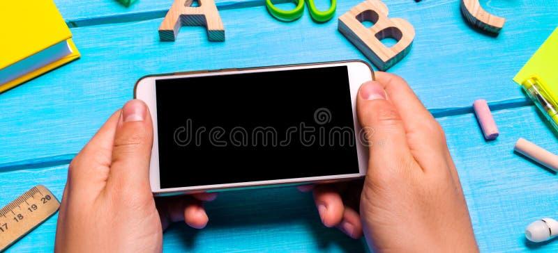 De student houdt een mobiele telefoon op de achtergrond van creatief op de Desktop knoeit de werkplaats van de student E stock afbeeldingen