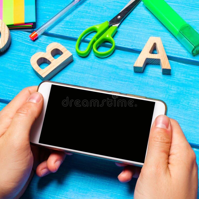 De student houdt een mobiele telefoon op de achtergrond van creatief op de Desktop knoeit de werkplaats van de student E royalty-vrije stock afbeelding
