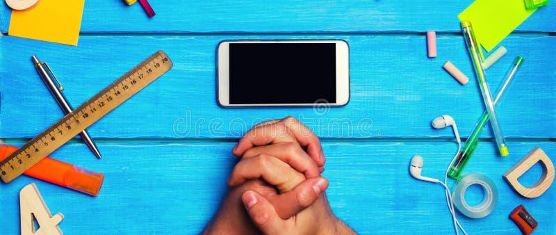 De student kruiste van hem indient voorzijde van een mobiele telefoon in de werkplaats Een plaats voor tekst Een student bekijkt  stock foto