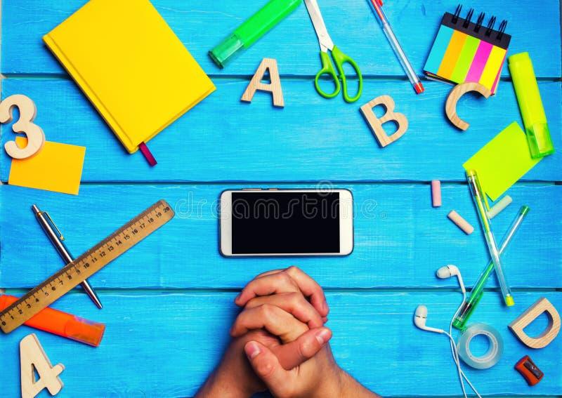 De student kruiste van hem indient voorzijde van een mobiele telefoon in de werkplaats Een plaats voor tekst Een student bekijkt  royalty-vrije stock foto's