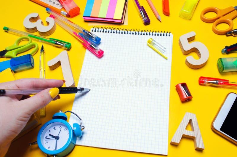 De student maakt nota's in een notitieboekje De ruimte van het exemplaar Schooltoebehoren op een bureau op een gele achtergrond C stock foto