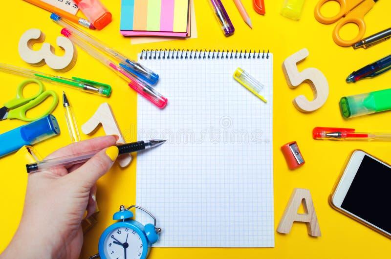 De student maakt nota's in een notitieboekje De ruimte van het exemplaar Schooltoebehoren op een bureau op een gele achtergrond C royalty-vrije stock foto's